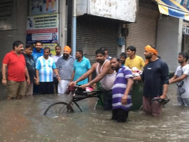 Phagwara MLA Som Parkash (fourth from left) and mayor Arun Kholsa (to his right) with local BJP workers standing in knee-deep water during rain in Phagwara on Saturday.