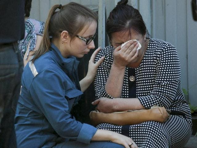 A Russian Emergency Situation employee, left, comforts a woman as colleagues and relatives of dead workers from Kyrgyzstan gather next to the burnt building of a printing plant's warehouse in Moscow, Russia, Saturday, Aug. 27, 2016.