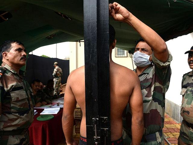 A youth stands as his height is measured at an army recruitment rally.