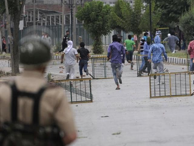 Policeman chase protesters following the killing of teenager Irfan Ahmed by security forces in downtown area of Srinagar, J-K, on Monday,August 22,2016.  Kashmir Valley has been witnessing violent protests  since July 8 when militant commander Burhan Wani was killed.