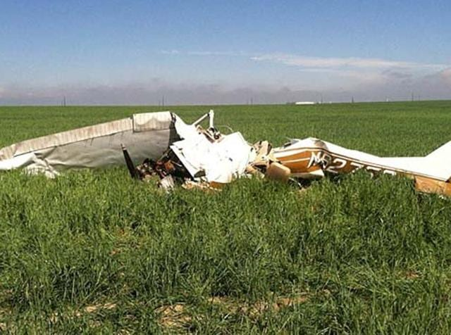 The wreckage of a crashed Cessna 150 plane lies in a field near Watkins, Colorado.