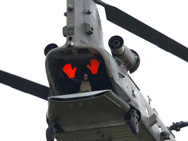 A crew member of a Chinook helicopter waves at the crowd during a flying display.