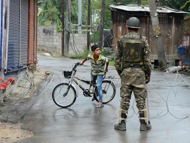 A paramilitary trooper stands guard as a Kashmiri child looks out from behind a barbed wire cordon during a curfew in Srinagar.