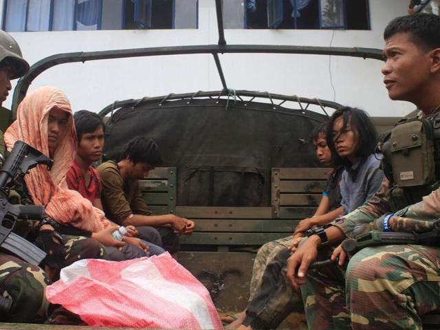This photo taken on August 23, 2016 shows Philippine soldiers guarding members of the Maute extremist group aboard a military vehicle in Marawi City in the southern island of Mindanao, a day after they were arrested at a military checkpoint and who were later on August 27 freed by their comrades in a daring jailbreak.