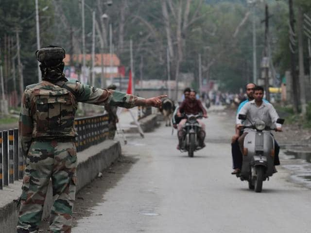A security personnel stops vehicles near Badami Bagh during restrictions in Civil Lines area of Srinagar, Jammu and Kashmir, on Saturday,August 27,2016. Authorities have decided to lift curfew from the valley except for some areas from August 29, 2016.
