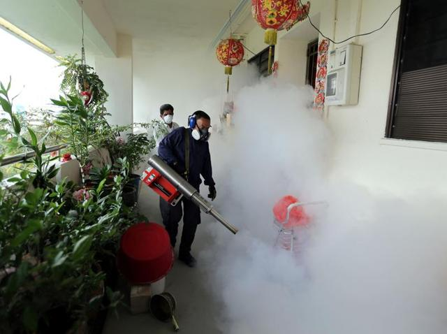 This photograph taken in Singapore on April 5, 2016 shows a worker fumigating an area against mosquitoes which carry the dengue virus at a residential estate.