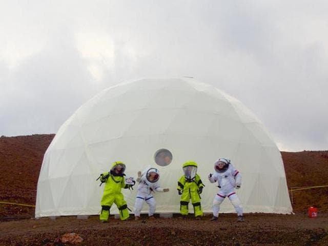In this photo provided by the University of Hawaii, six scientists celebrate as they exit from their Mars simulation habitat on slopes of Mauna Loa on the Big Island, Hawaii on Sunday. The scientists completed a yearlong Mars simulation in Hawaii on Sunday, where they lived in the dome in near isolation.
