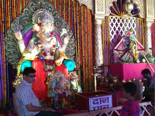 An idol of Lord Ganesha adorned with flowers, garlands and jewellery.