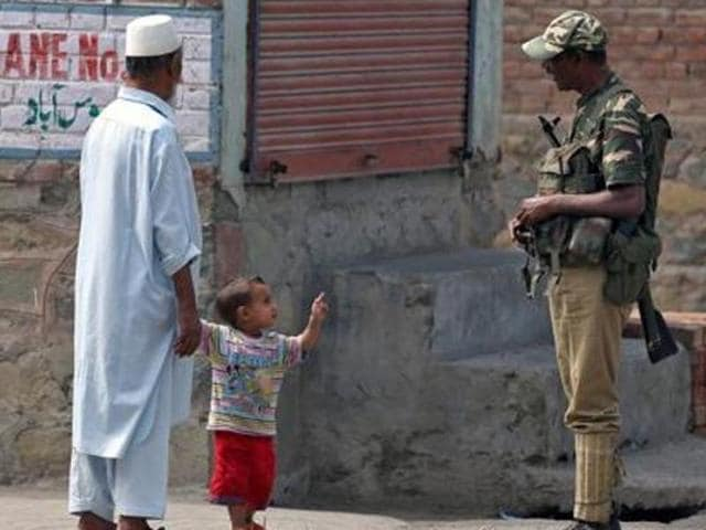 A boy gestures at a member of the security forces in Srinagar.