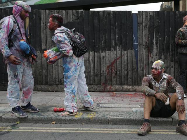 Revellers stand on the pavement in front of boarded up houses on the first day of the Notting Hill Carnival in west London on Sunday.
