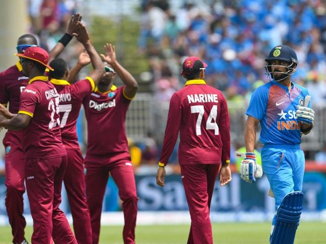 Virat Kohli (R) of India walks off the field dismissed by Dwayne Bravo of West Indies (L) as West Indies players celebrate during the 1st T20i between West Indies and India at Central Broward Stadium in Fort Lauderdale, Florida, on August 27, 2016. / AFP PHOTO / Randy BROOKS