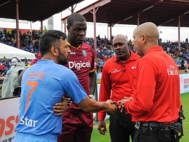 MS Dhoni and Carlos Brathwaite (2L) of West Indies agree with umpires Patrick Gustard (2R) and Joel Wilson (R) to abandon their match due to rain during the 2nd and final T20i between West Indies and India at Central Broward Stadium August 28, 2016 in Fort Lauderdale.