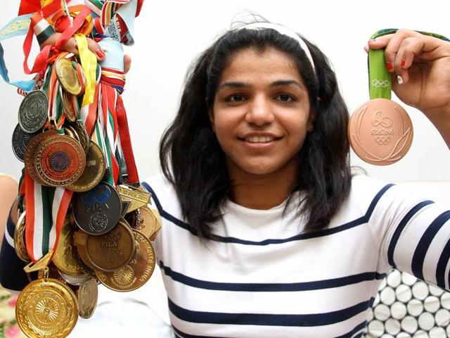 Sakshi Malik holding all her previous won medals in one hand and her recent Olympic bronze in the other.