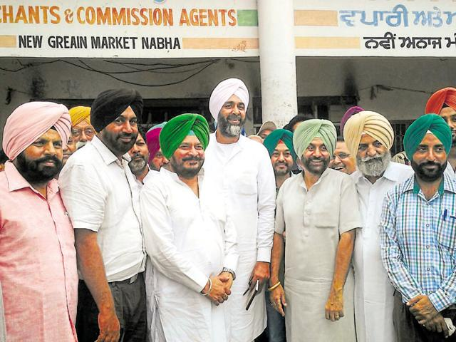 Manpreet Singh Badal and Sadhu Singh Dharmsot with commission agents at the New Grain Market in Nabha on Monday.