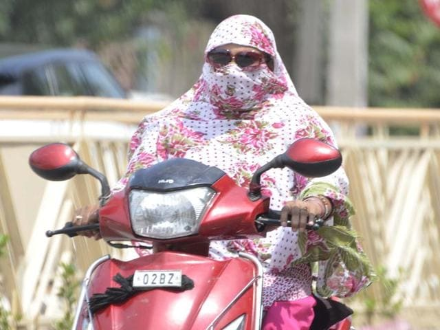 A girl driving her two-wheeler with covered face in Amritsar on Monday.