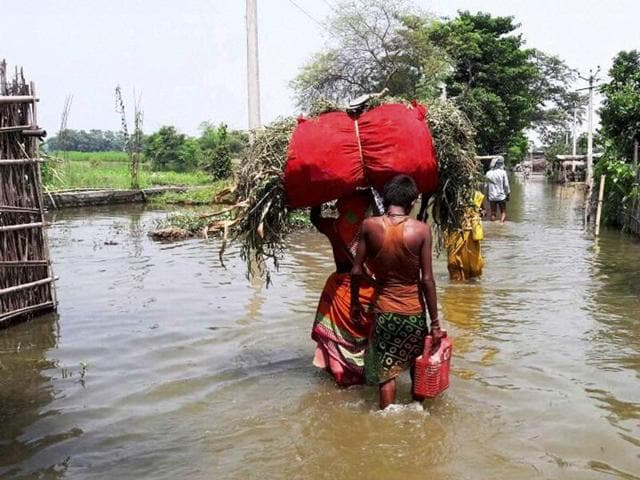 Villagers wade though a flooded area in Katihar district of Bihar on Sunday.
