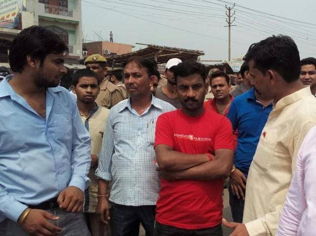 Locals gather in protest after the body of a one-year-old was found at the railway tracks near Loni railway station on Monday.