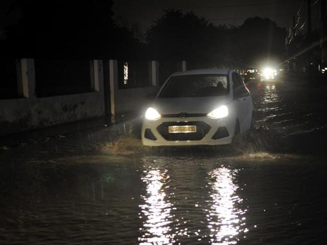 A car wades through a waterlogged road in Gurgaon.(Abhinav Saha/HT Photo)