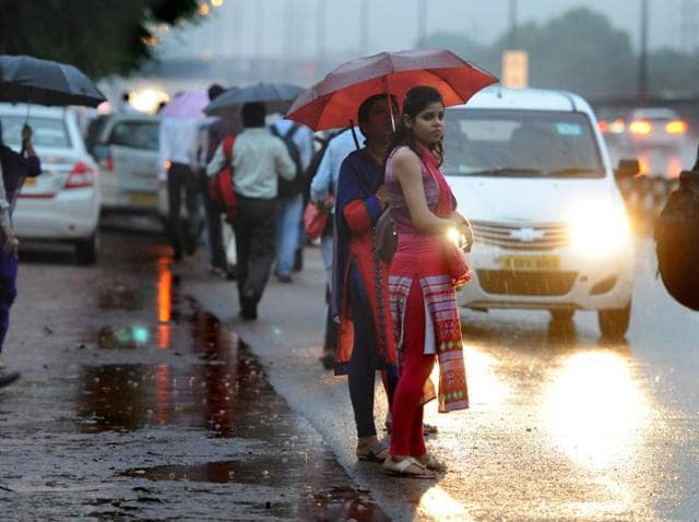 People wait for public transport in rain at Delhi-Gurgaon expressway, in Gurgaon.