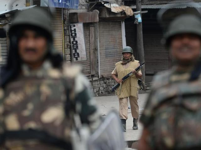 A security force personnel holds a pellet gun as he patrols in Srinagar.