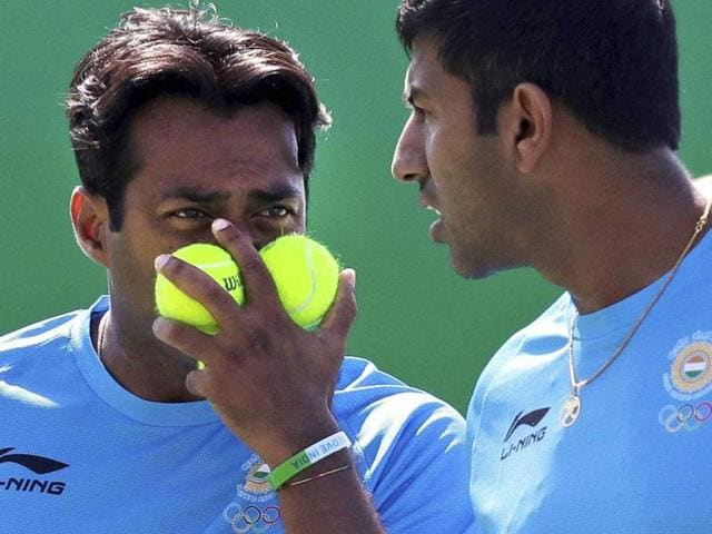 Leander Paes, of India, blocks his face with tennis balls as he talks with his partner Rohan Bopanna.
