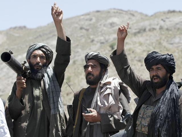In this May 27, 2016 file photo, Taliban fighters react to a speech by a senior leader of a breakaway faction of the Taliban, Mullah Abdul Manan Niazi, in the Shindand district of Herat province, Afghanistan.
