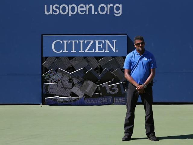 An official stands waiting for a fallen match clock board to be fixed inside Court 17 during the match between Gael Monfils, of France, and Gilles Muller, of Luxembourg.
