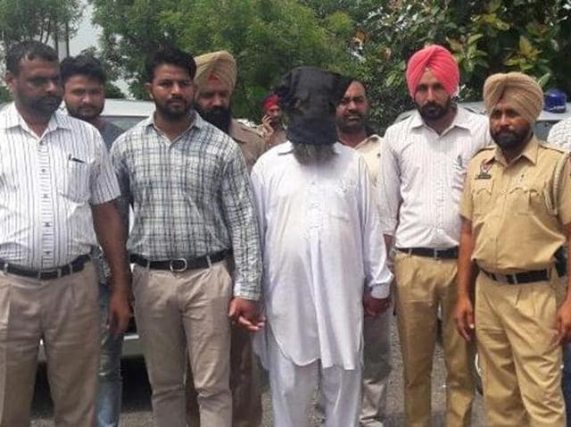The accused, with his face covered, in police custody in Fatehgarh Sahib on Tuesday.