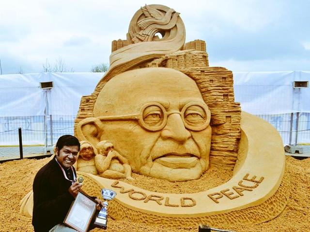 Sand artist Sudarsan Pattnaik with his art -- 'Mahatma Gandhi sculpture for non-violence and peace'.