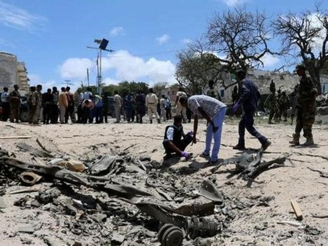 Security forces assess the scene of a car bomb claimed by al Shabaab Islamist militants outside the president's palace in the Somali capital of Mogadishu.