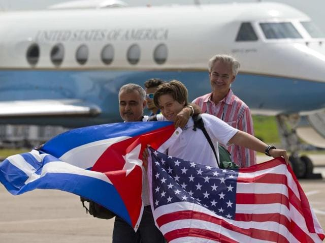Passengers of JetBlue flight 387 hold United States and Cuban national flags at an airport in Santa Clara, Cuba.