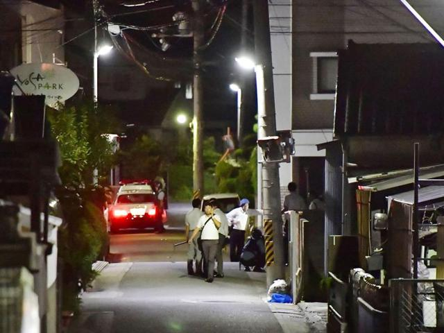 Yasuhide Mizobata, a murder suspect, holding guns sits on scaffoldings as he holed up at an apartment in a standoff after he fired at a police car and escaped, in Wakayama, central Japan.