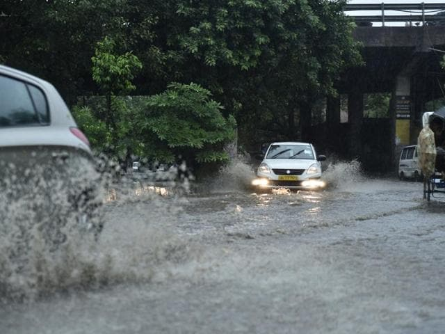 People wade through  water-logged road due to heavy rain near AIIMS, in New Delhi on Wednesday, August 31, 2016.