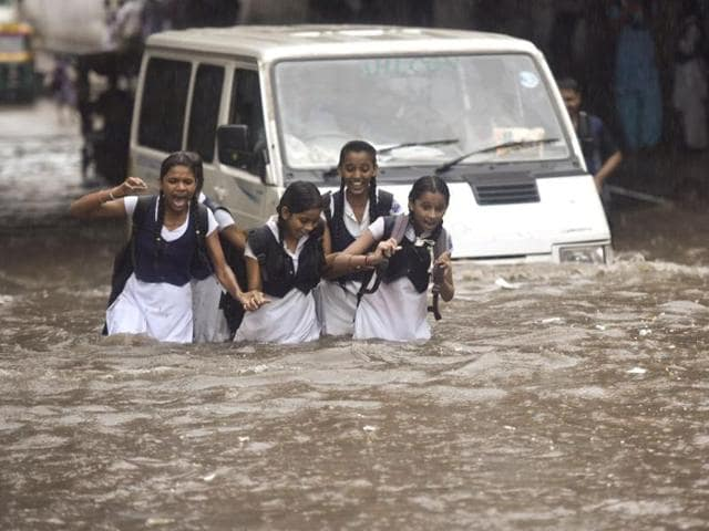 School students wade through a waterlogged road in New Delhi on Wednesday.