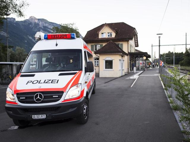 A police car stands at the train station following an attack on board a train in Salez, Switzerland.