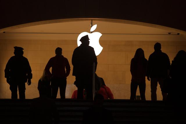 A police officer is silhouetted against the Apple logo in Manhattan.