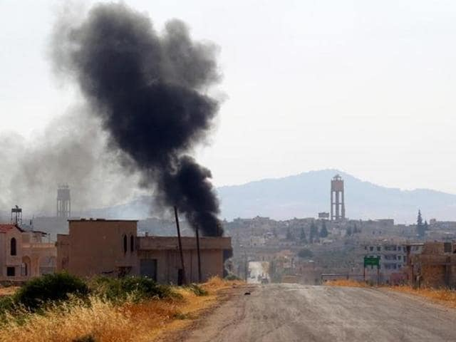 Smoke rises from Taybat al Imam town after rebel fighters from the hardline jihadist Jund al-Aqsa advanced in the town in Hama province.