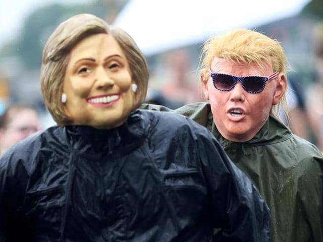 Volunteers wear masks of presidential candidates Hillary Clinton and Donald Trump during a march in Philadelphia, Pennsylvania, on July 28, 2016.