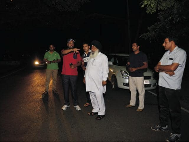 Crime branch officials at the spot from where the car was snatched in Sector 15 on Thursday.