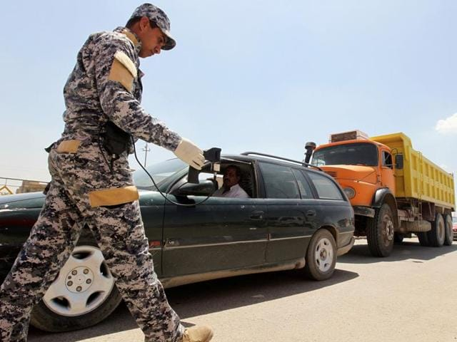 A policeman uses a scanning device to inspect a vehicle at the entrance to Sadr City, northeastern Baghdad in April.