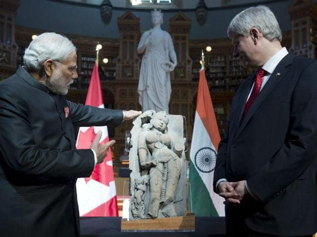 Canadian prime minister Stephen Harper, right, and Prime Minister Narendra Modi look at the sculpture of