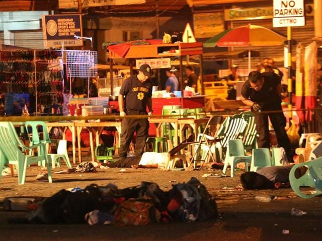 A Philippine soldier keeps watch at a blast site at a night market that has left several people dead in southern Davao city.