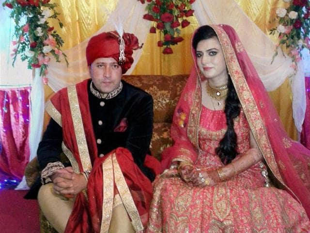 Owais Geelani poses for a photo with his bride from Pakistan-occupied Kashmir at their wedding function in Srinagar.