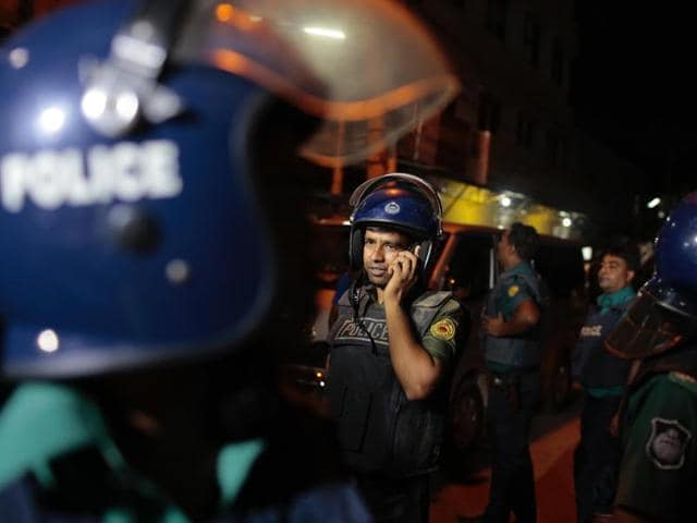 A Bangladeshi policeman speaks on a mobile phone at the scene of a raid on a suspected militant hideout in Dhaka on Friday.