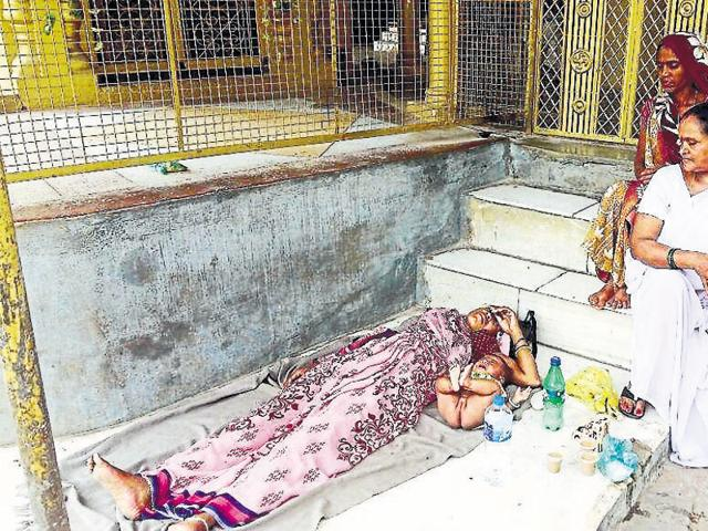 Urmila, along with her baby, lying on the road after she was thrown out of the district hospital ward in Chattarpur.