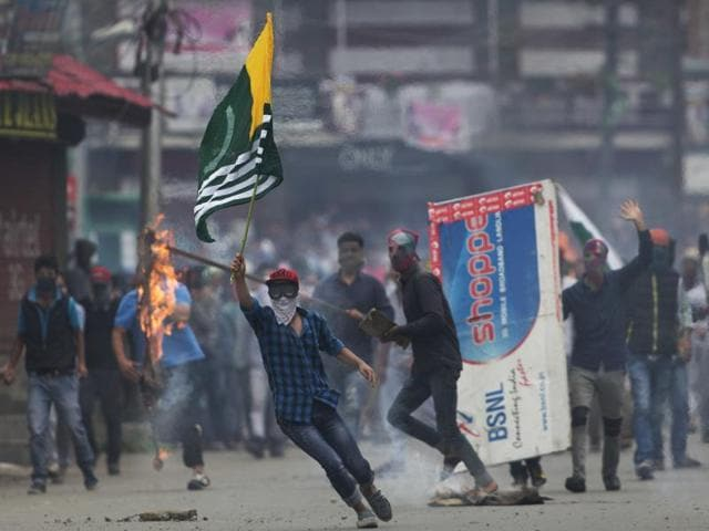 A protester holds a flag of Pakistan occupied Kashmir during a protest in Srinagar,  Thursday, Sept. 1, 2016.