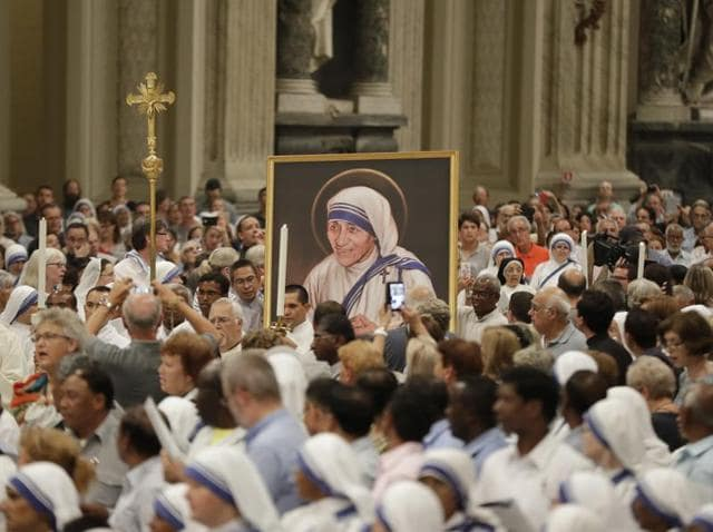 A portrait of Mother Teresa is carried in the crowd during a vigil of prayer in preparation for her canonisation in the St. John in Latheran Basilica at the Vatican.