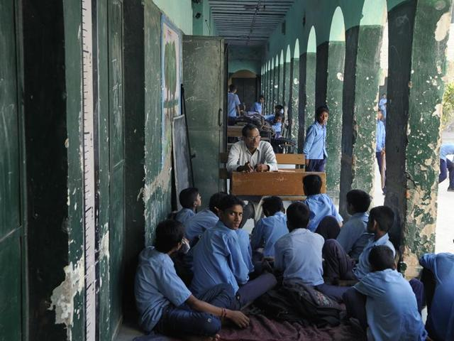 A file picture of a teacher taking class at a school in Badarpur, New Delhi. Many teachers in government schools such as this are forced to take classes outside the classrooms because of lack of space.