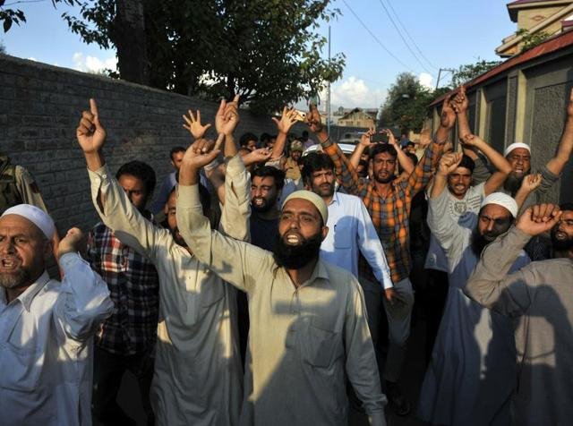 Supporters of Syed Ali Geelani, the Chairman of All Parties Hurriyat (Freedom) Conference (APHC) raise pro-freedom slogans in front of the cavalcade of the all-party delegation of parliamentarians outside his residence on Sep 4, 2016.(Waseem Andrabi / HT Photo)