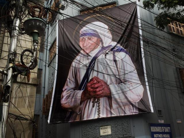 Nuns of the Missionaries of Charity in Kolkata walk past a large banner of Mother Teresa ahead of her canonisation.